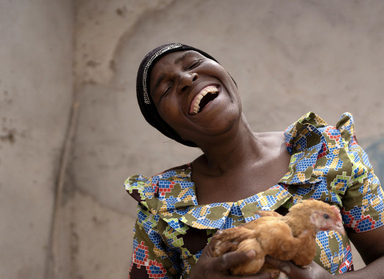 Happy woman holding a chicken